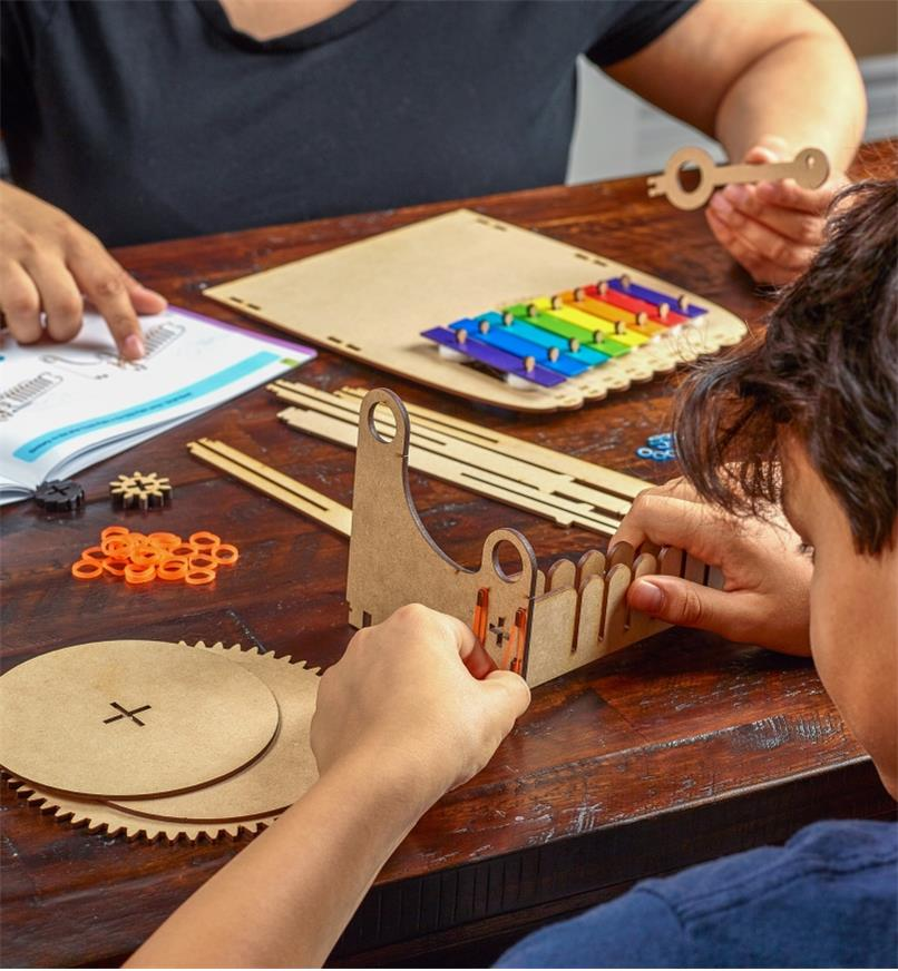 A young person and an adult helper assemble the xylophone music machine kit