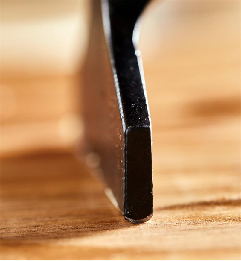 A close view of a Picard veneer hammer's rounded edge being drawn across a veneered surface
