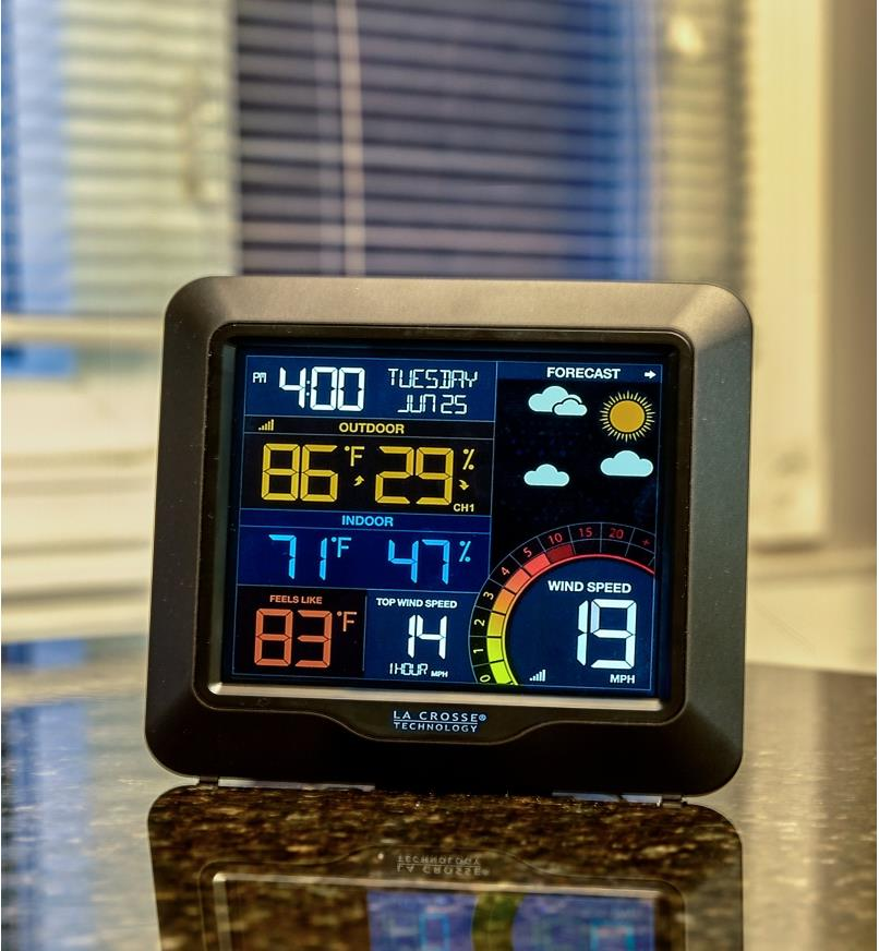 LCD screen of the wireless weather station displays date, time, forecast icons, temperature and humidity in Fahrenheit and wind speed in miles per hour