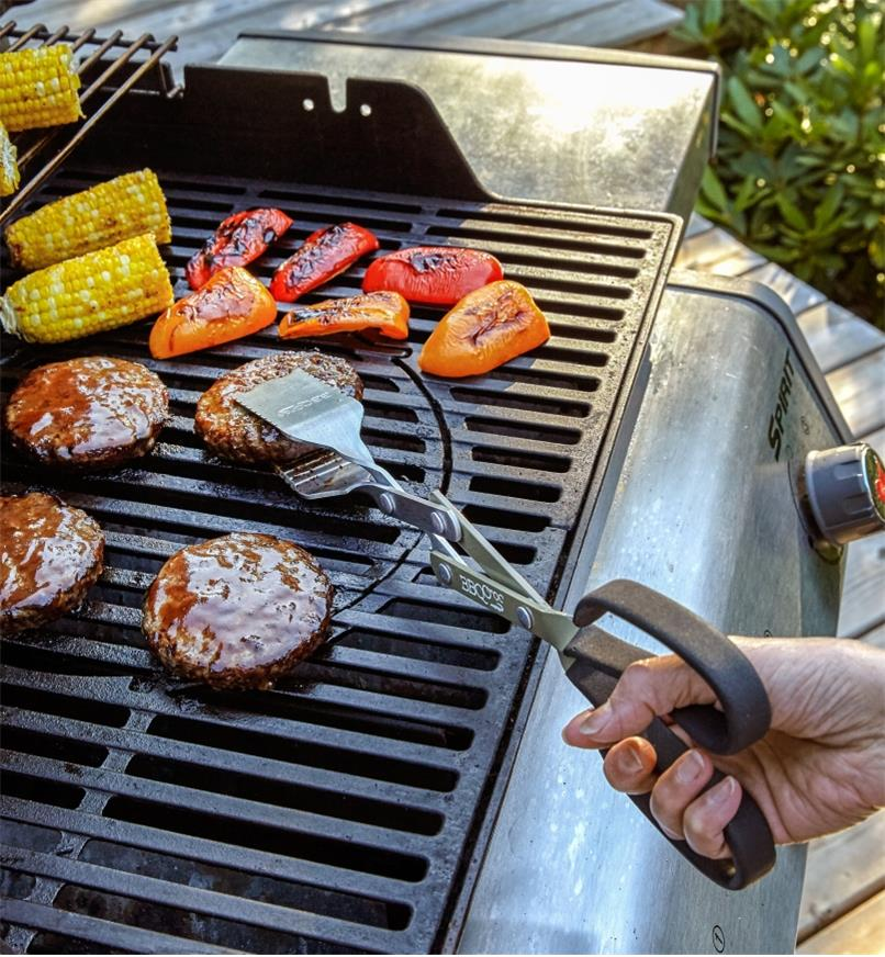 BBQ Croc tongs picking up a hamburger in the center of a grill