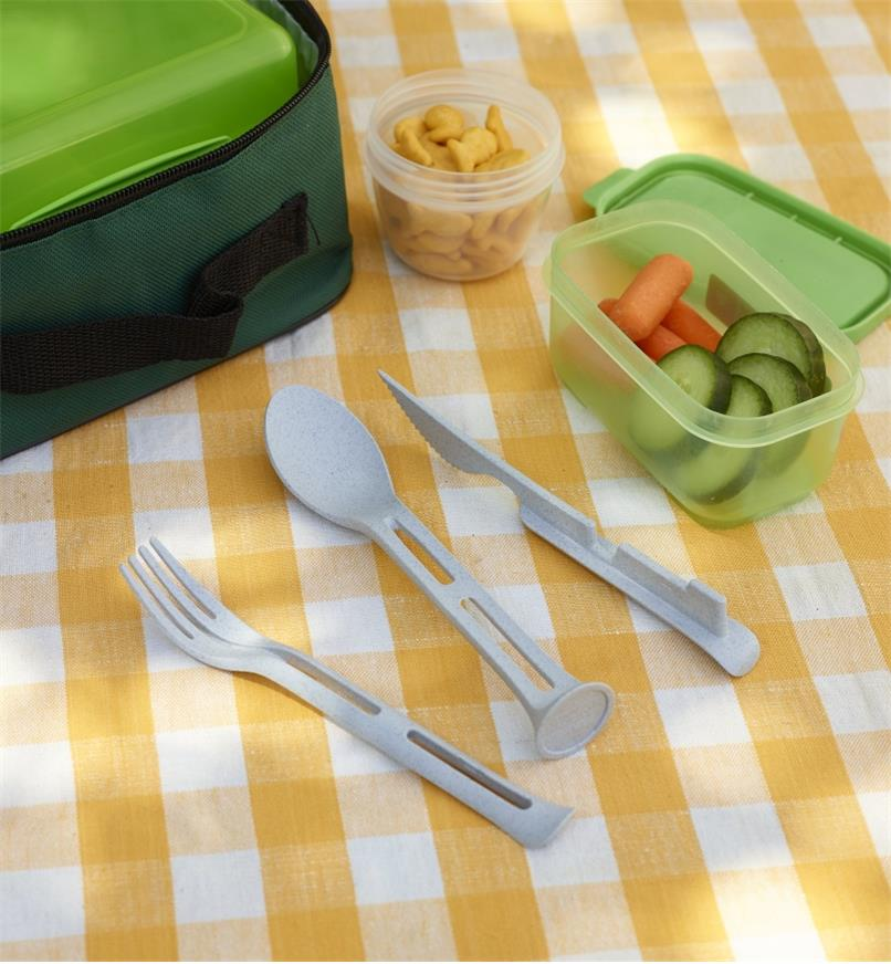 Gray Klikk small cutlery set taken apart to show the knife, fork and spoon next to containers of food