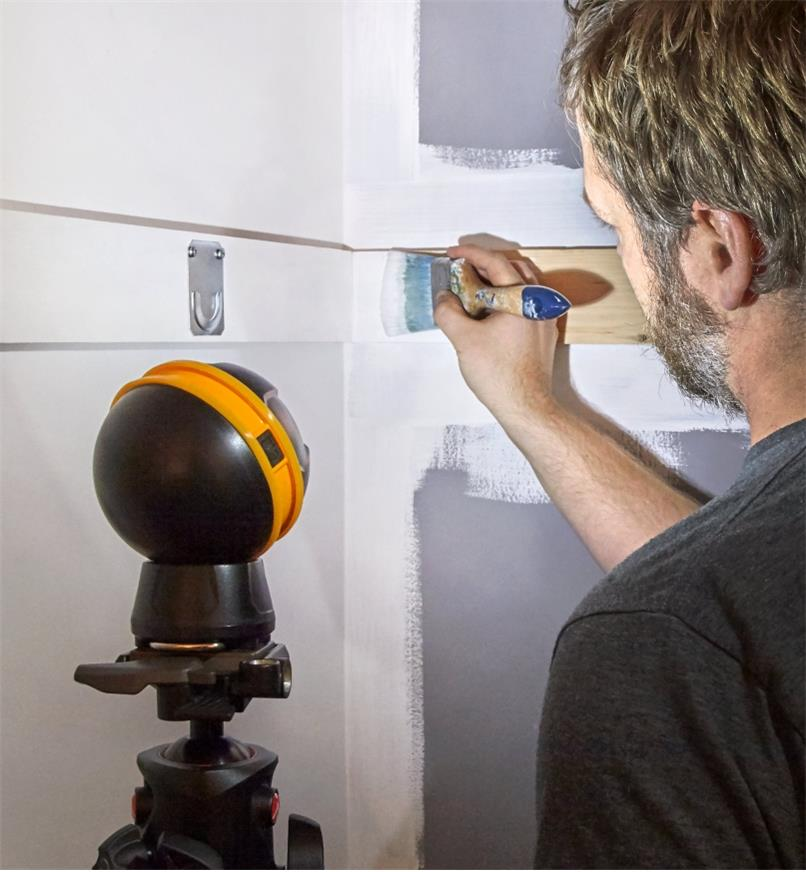 A rechargeable orb light mounted on a tripod to illuminate inside a closet that is being painted