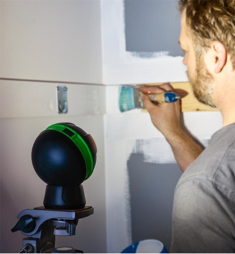 A battery-powered orb light mounted on a tripod to illuminate inside a closet that is being painted