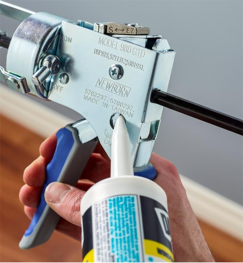 Trimming the nozzle of a caulk tube using the spout cutter