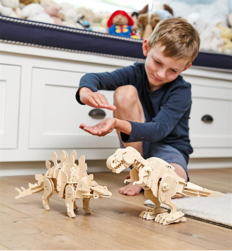 A boy claps his hands to activate the assembled walking dinosaur models
