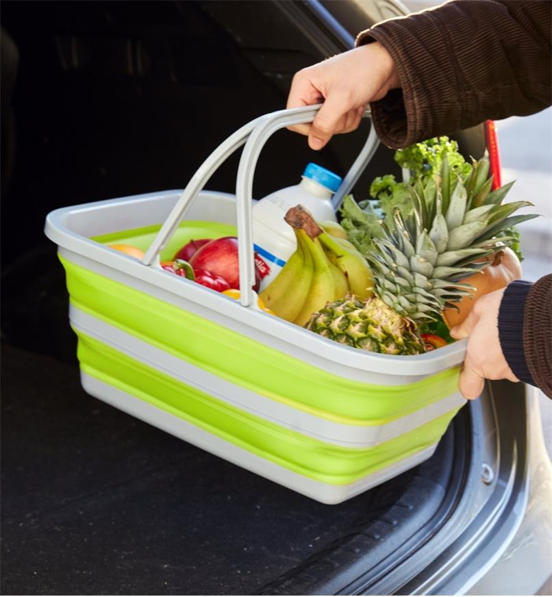 A collapsible tote filled with groceries is placed in a car trunk