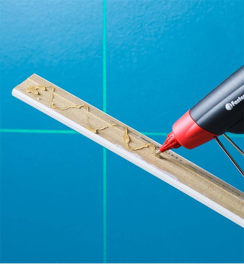 Installing a piece of trim molding, using a FastenMaster pro hot-melt gun to glue it in place