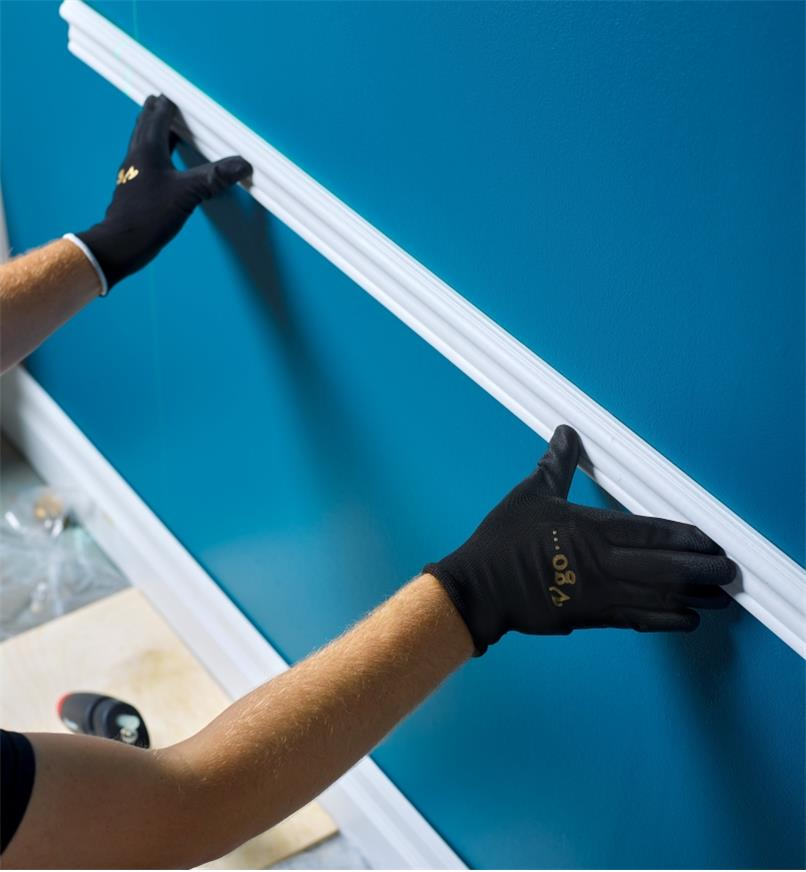 Installing a section of chair rail, using a FastenMaster pro hot-melt gun to glue it in place