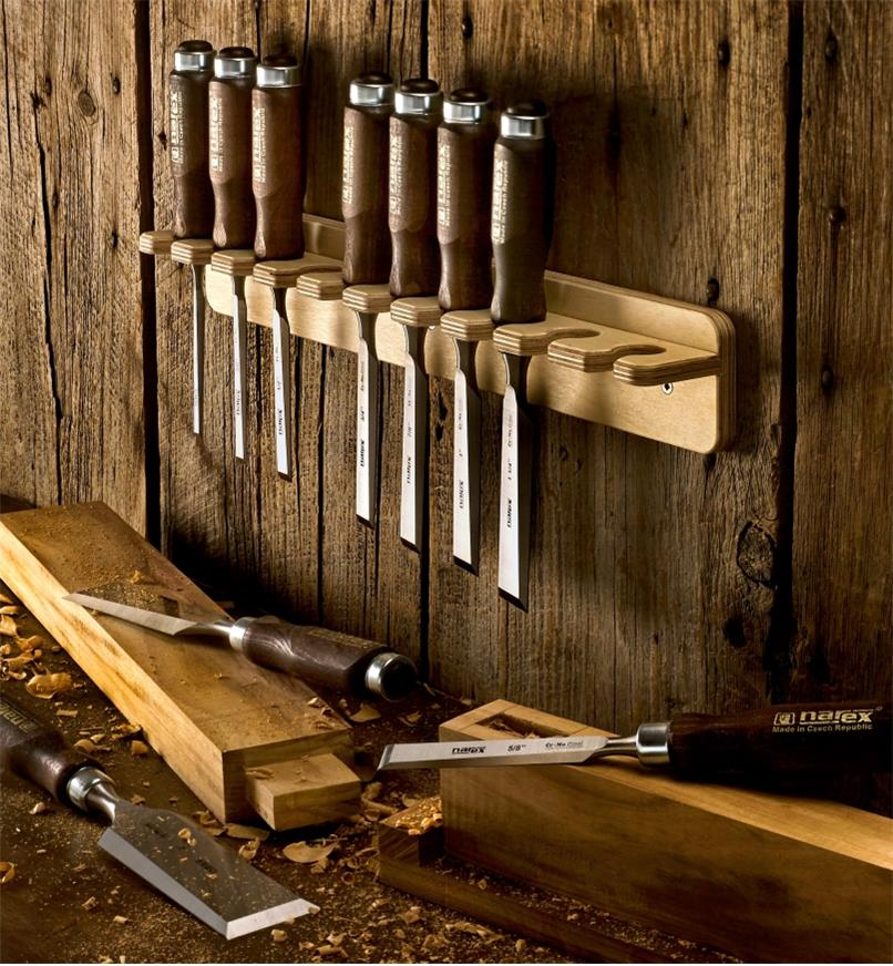 Seven Narex bevel-edge chisels in a wall rack and three on a workbench with mortise and tenon parts