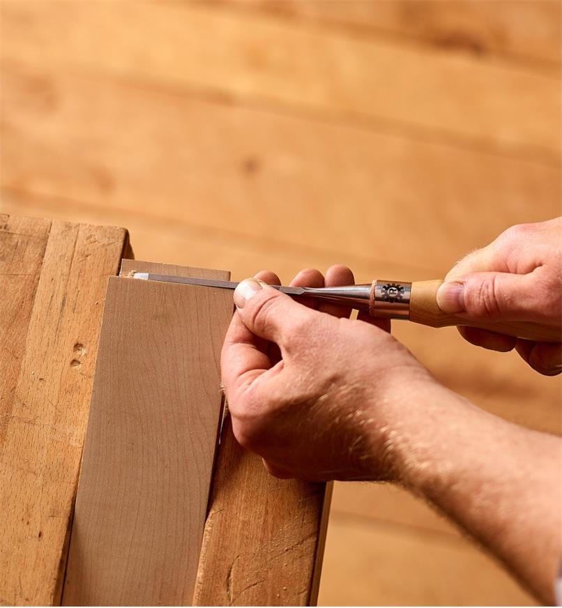 "A woodworker uses a 1/8"" Narex Richter chisel to trim a tenon"