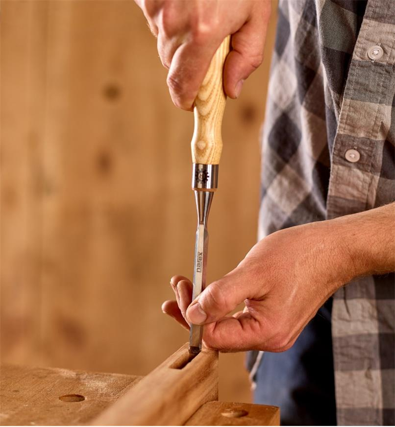 "A woodworker uses a 3/8"" Narex Richter chisel to smooth the walls of a mortise"