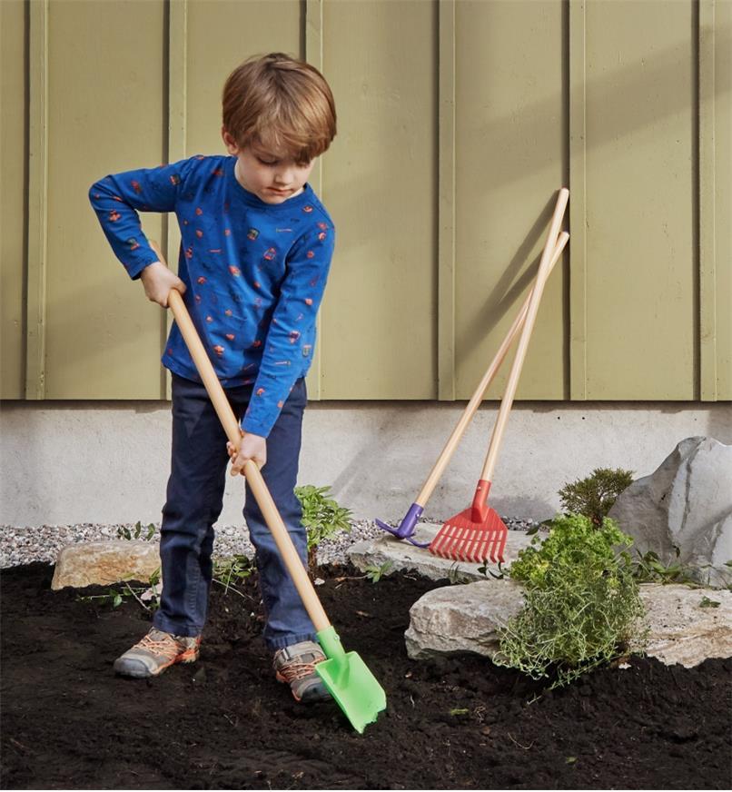 Enfant creusant dans le jardin à l'aide de la bêche de l'ensemble d'outils de jardinage pour enfants