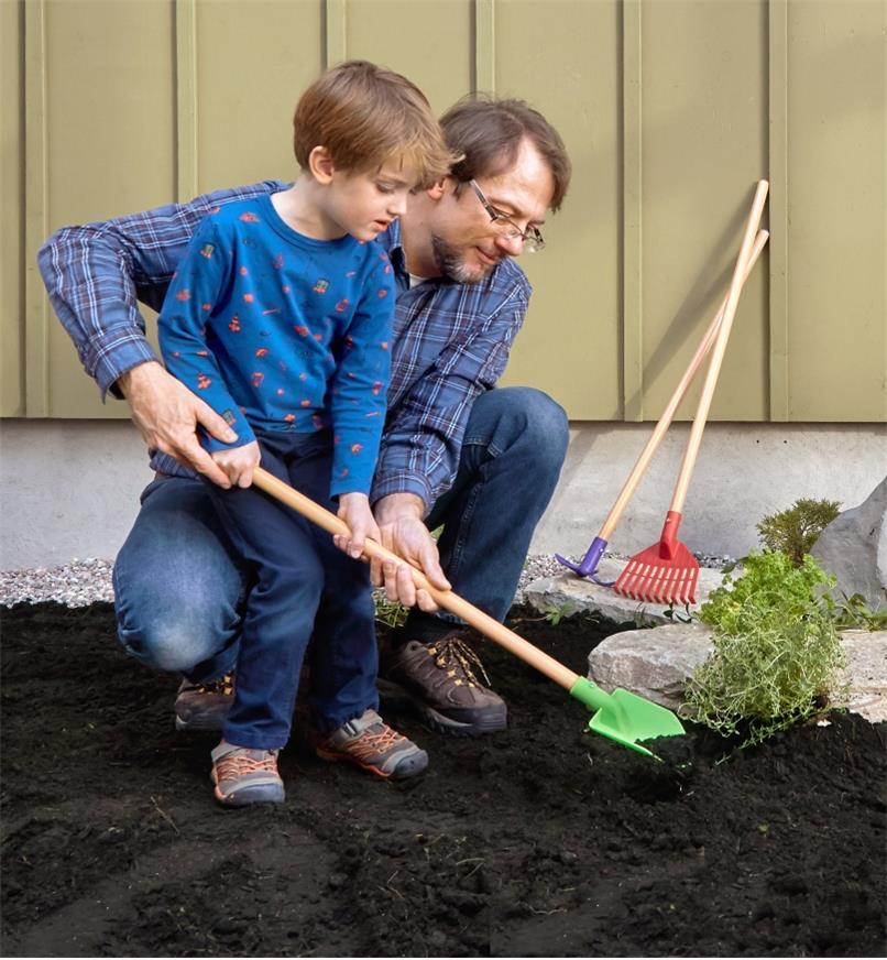 Adulte aidant un enfant qui creuse dans le jardin à l'aide de la bêche de l'ensemble d'outils de jardinage pour enfants