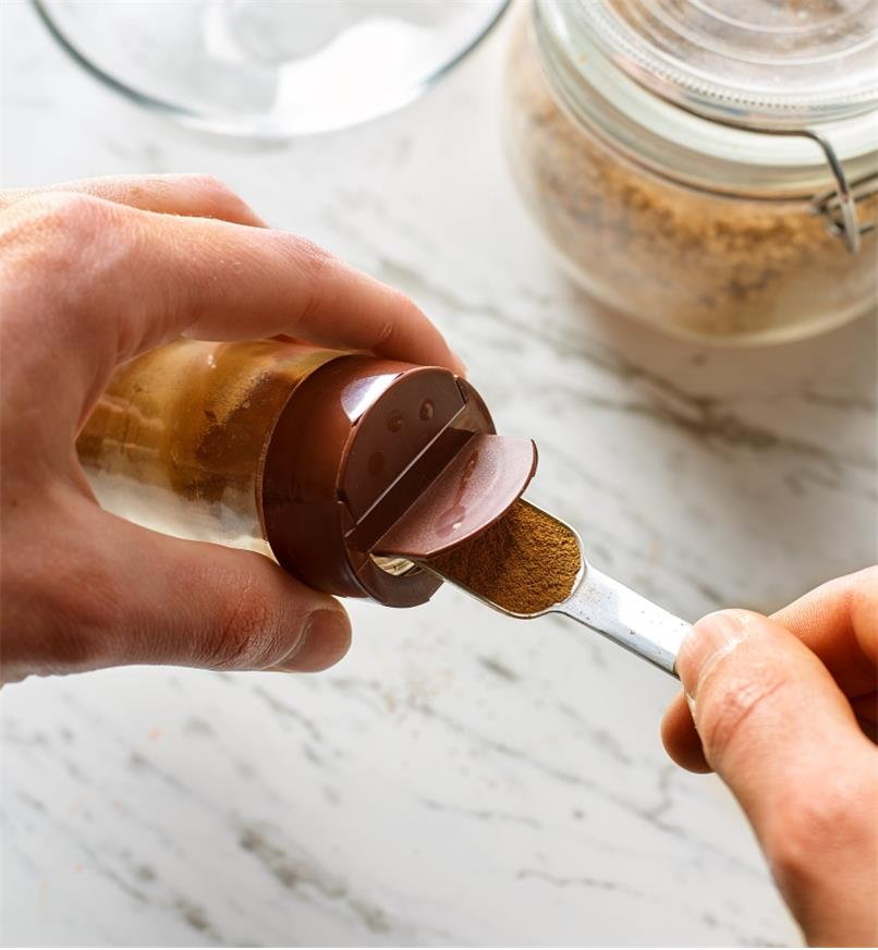 A spice jar measuring spoon in the mouth of a spice container