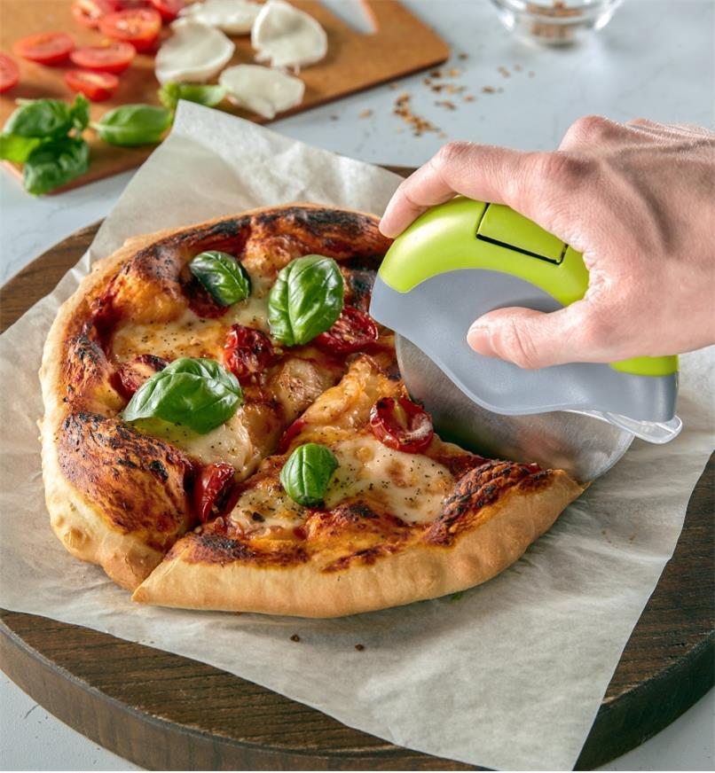 Pizza cutter slicing a cooked pizza