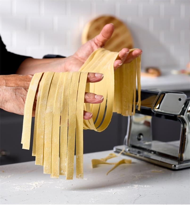 A cook holds lasagnette noodles made with a Marcato pasta machine and a lasagnette cutter attachment