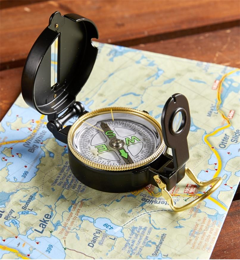 Open engineer's compass placed on a map