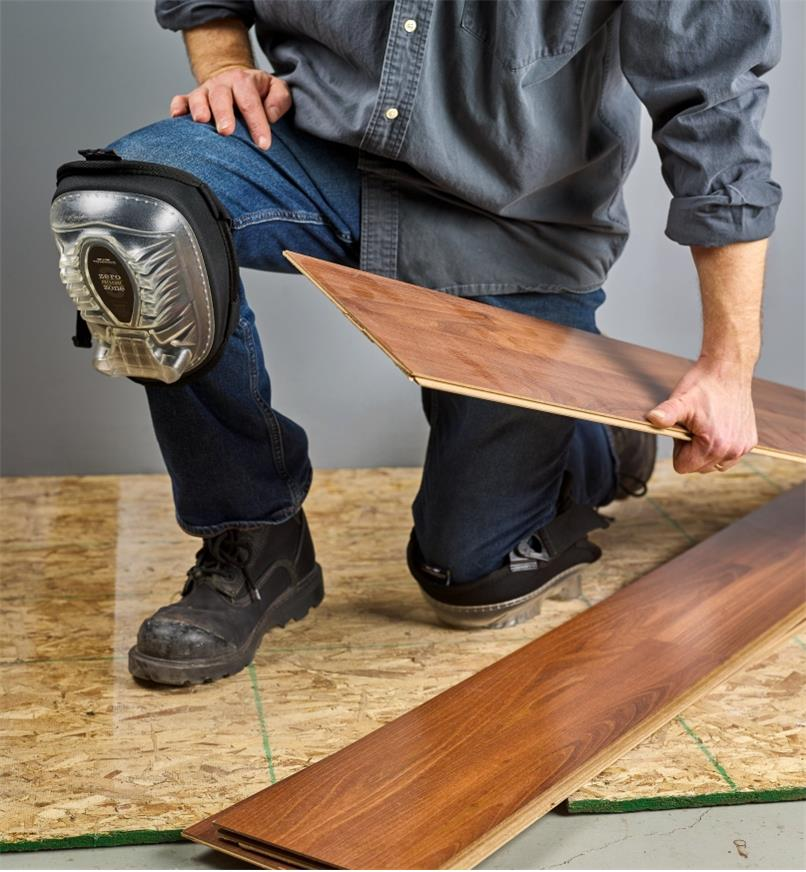 A man kneeling with the small premium knee pads to lay laminate flooring
