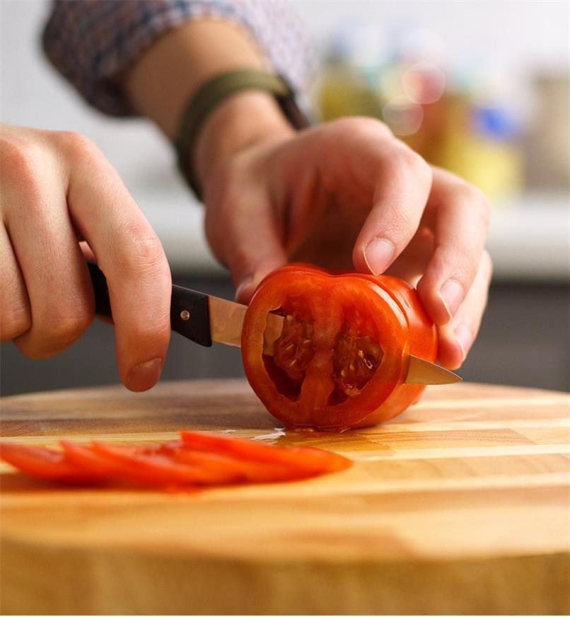 Couteau à légumes à dents ultra-fines tranchant une tomate