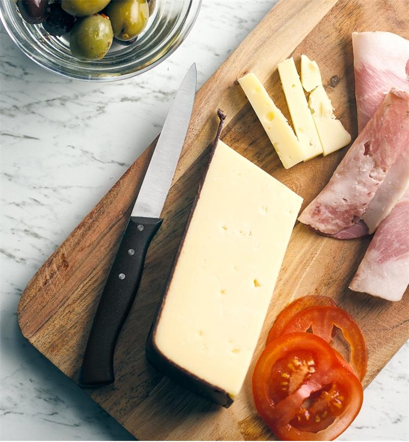 The serrated paring knife on a board with meat, cheese and tomato slices