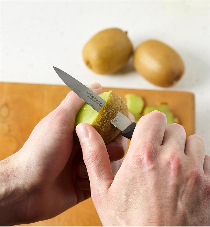Peeling a kiwi fruit with the serrated paring knife