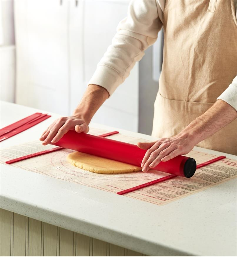 Rolling dough with the rolling pin on the dough mat between thickness guides