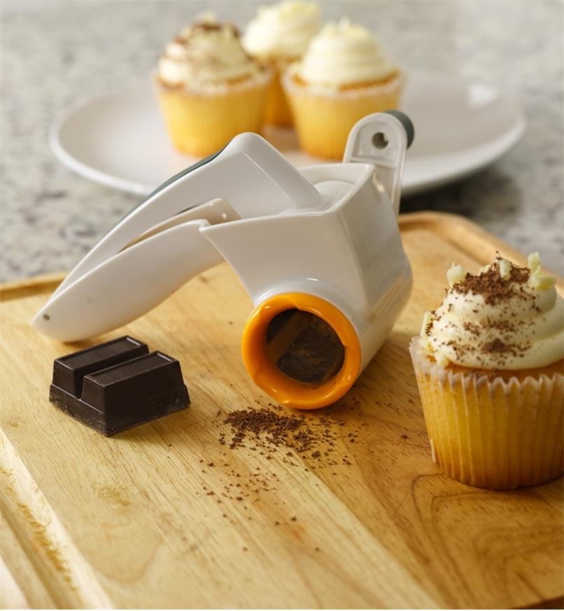 The rotary cheese grater next to cupcakes topped with grated chocolate