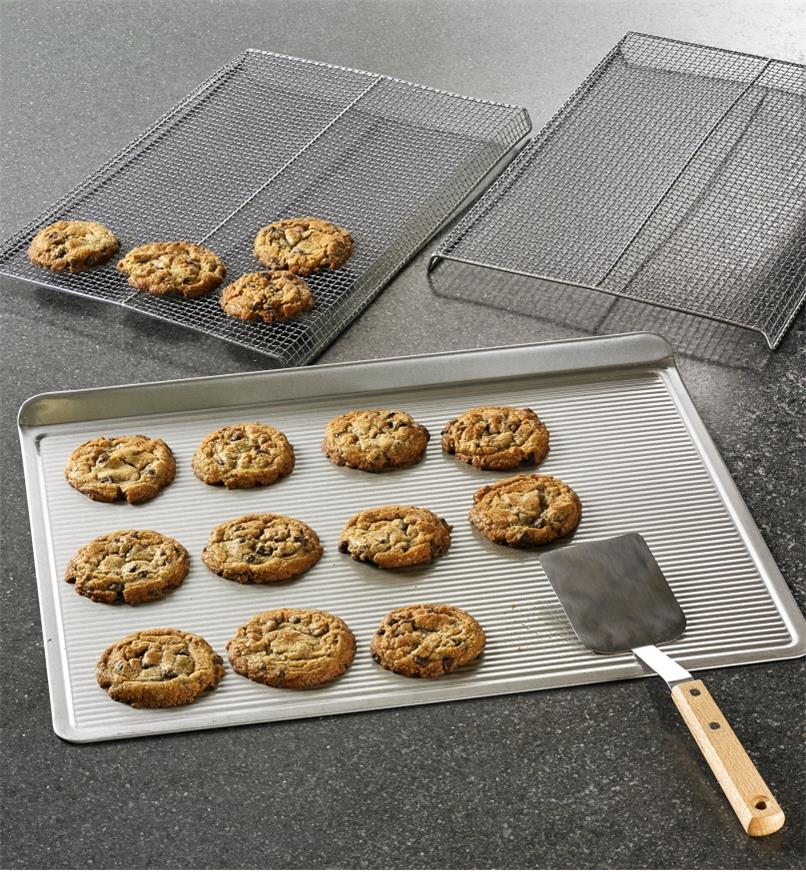 The cookie sheet, cookie racks and stainless-steel spatula being used to make a batch of cookies