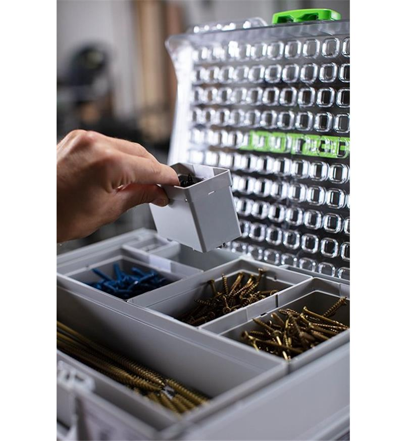 A bin is inserted into an open space in an organizer filled with bins containing hardware