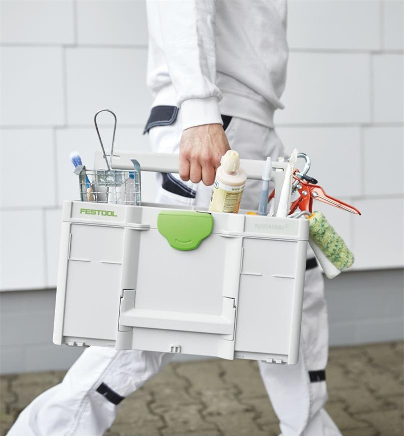 A worker carries a ToolBox SYS3 TB M 237 filled with painting supplies