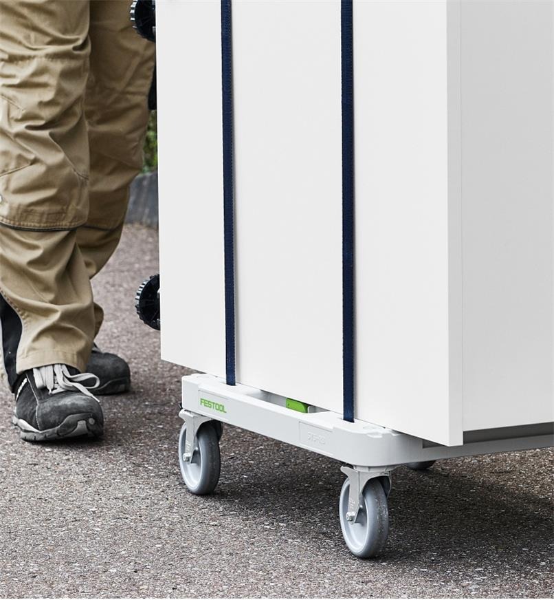 A cabinet strapped to a SYS-RB Dolly is pushed by a worker