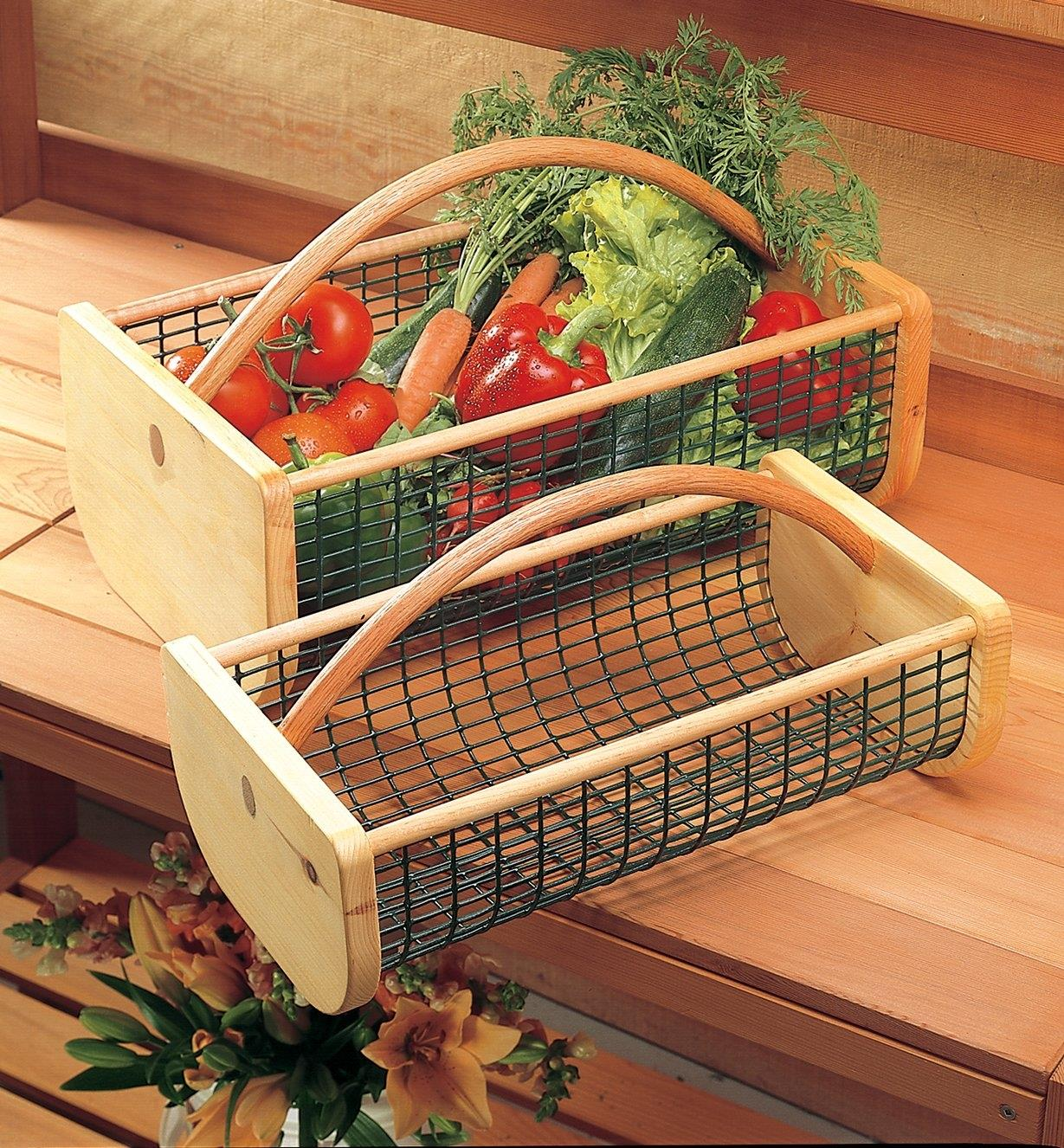 Large hod filled with vegetables next to an empty medium hod, sitting on a potting bench