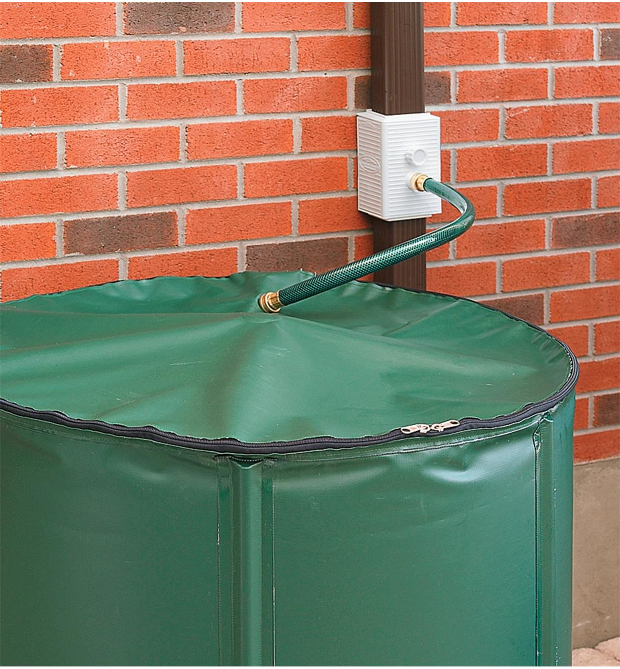 A Universal Downspout Diverter attached to a downspout and a hose leading to a rain barrel
