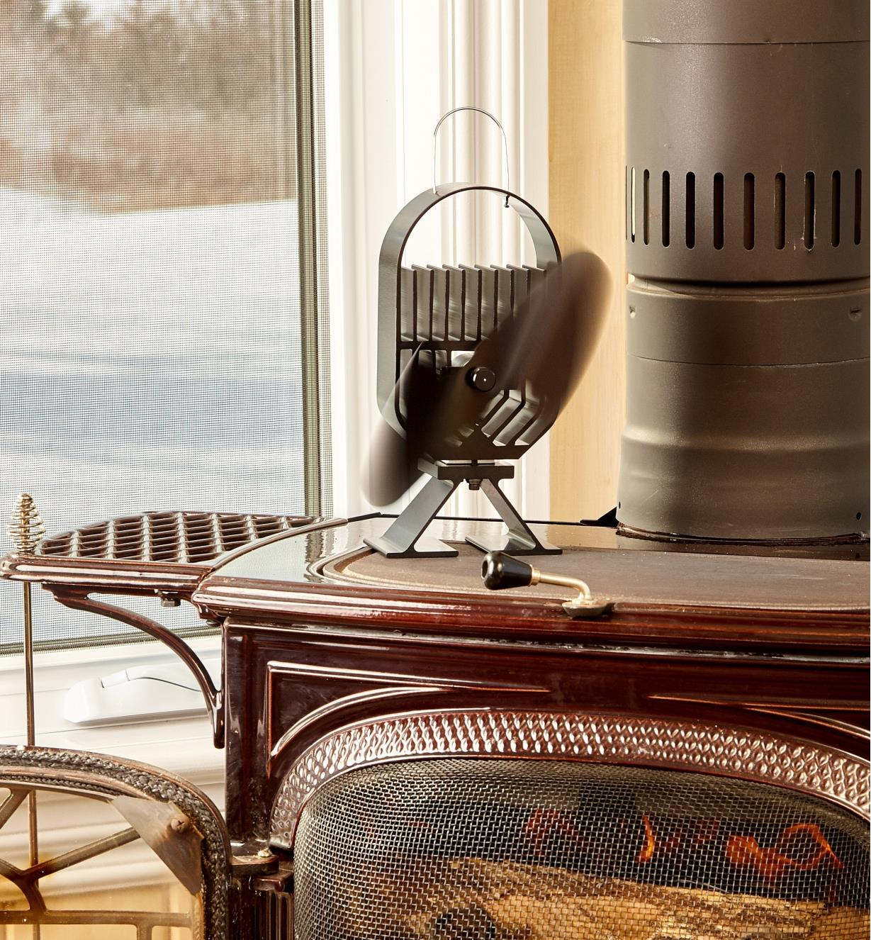 Small Ecofan AirDeco on a wood stove, distributing the heat of the fire