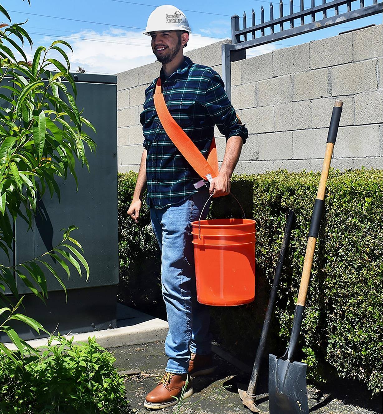 A man uses a Bucket Buddy Sash to help carry a heavy load in a pail
