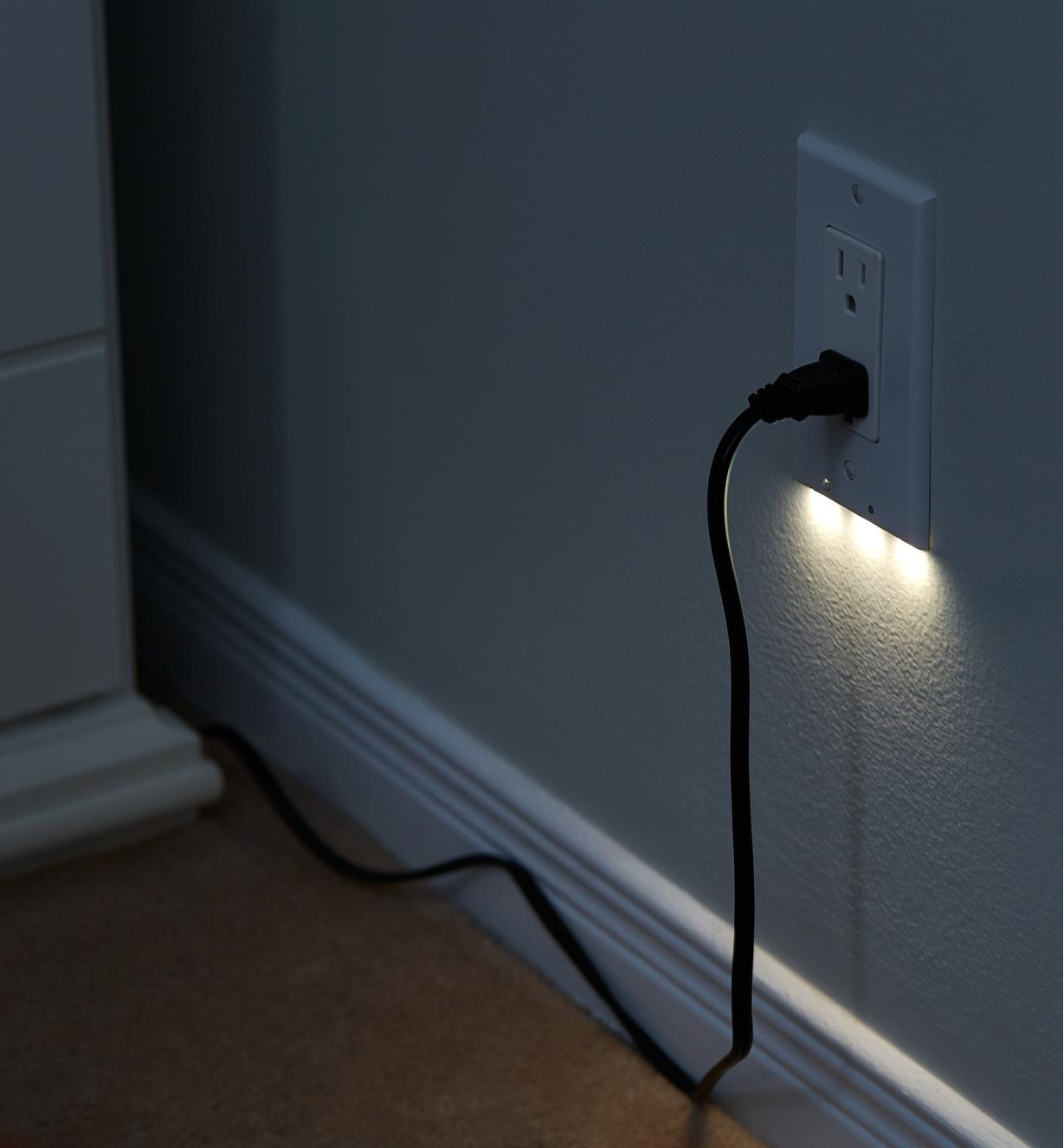 A Decora-style LED outlet cover plate mounted on a wall, giving gentle, diffused lighting at night.