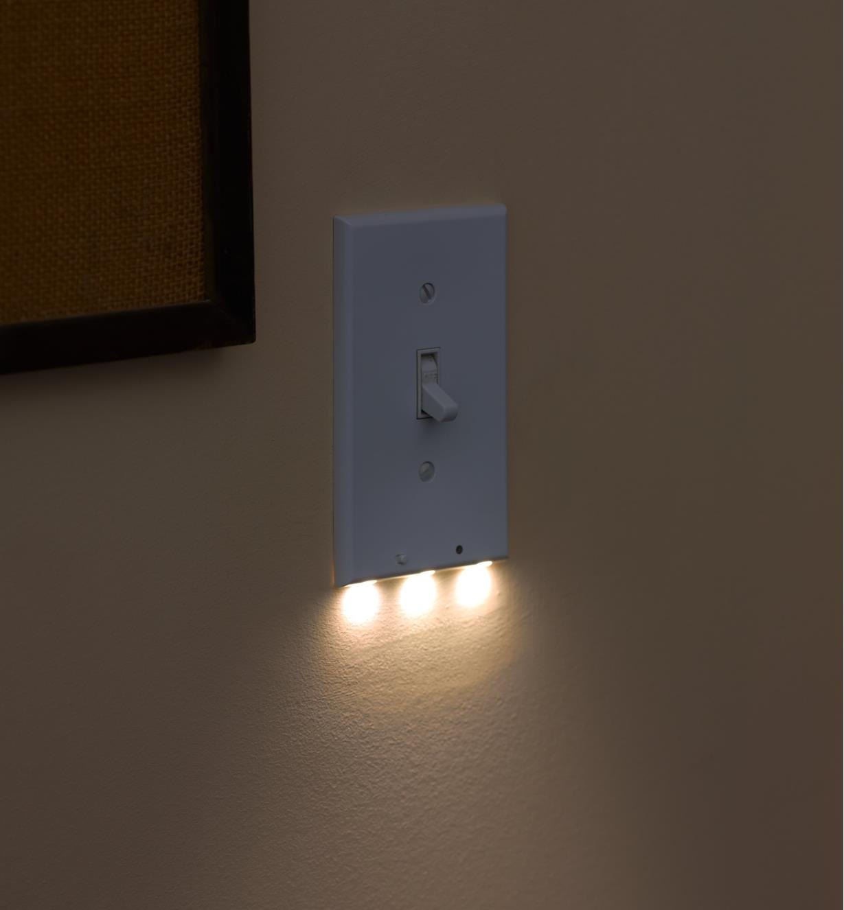An LED toggle switch cover plate mounted on a wall, giving gentle, diffused illumination at night.