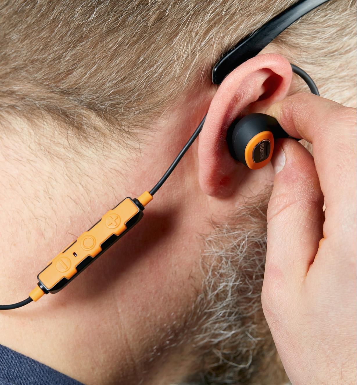 Homme insérant un écouteur antibruit électronique avec fil ISOtunes Pro 2.0 dans son oreille