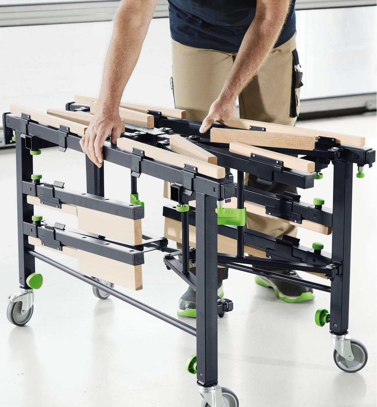 A man folding the mobile sawing table to a more compact size