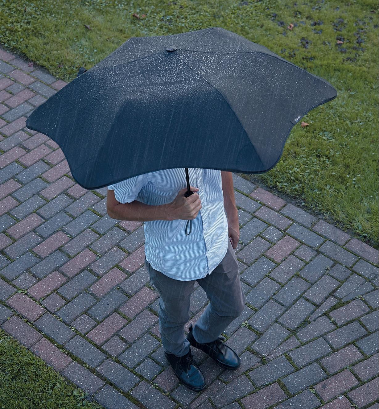 A man walks down a path in the rain carrying an XS Metro Compact Umbrella