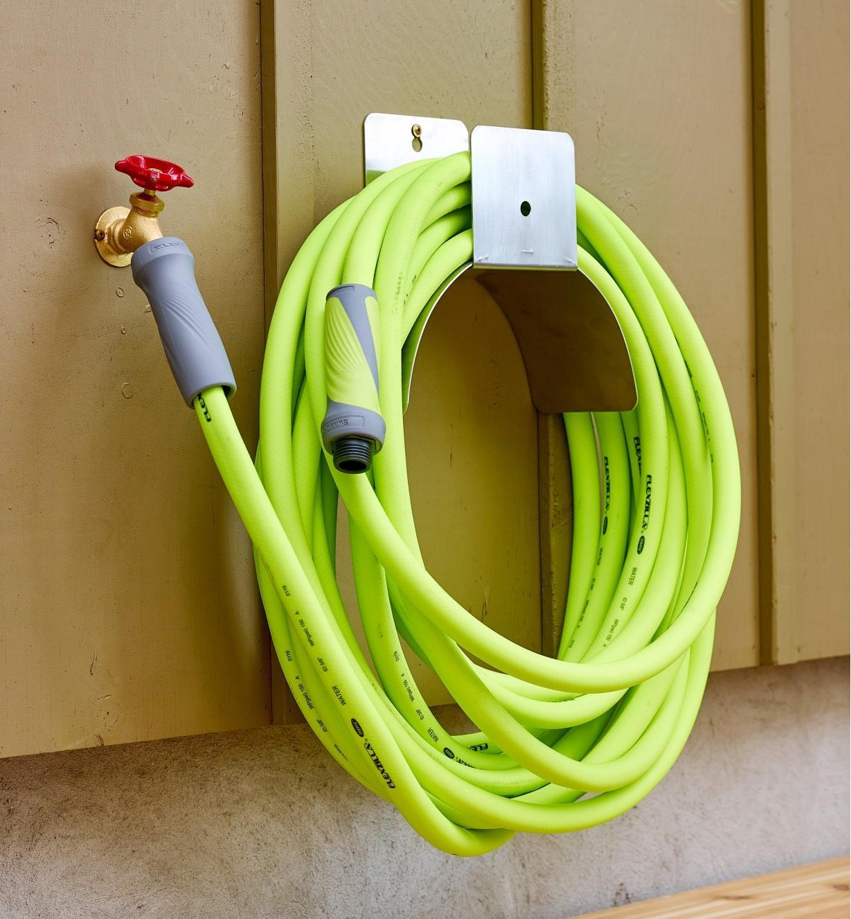 A coiled Flexzilla swivel-grip garden hose connected to a faucet