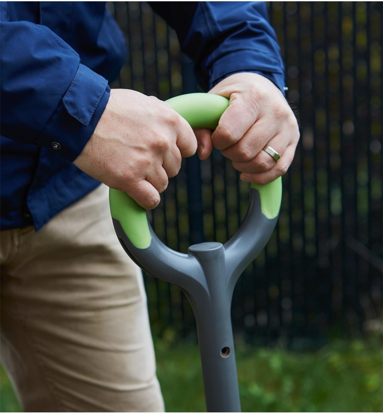 Gros plan sur les mains d'un homme agrippant la poignée d'une fourche ergonomique Radius en acier inoxydable