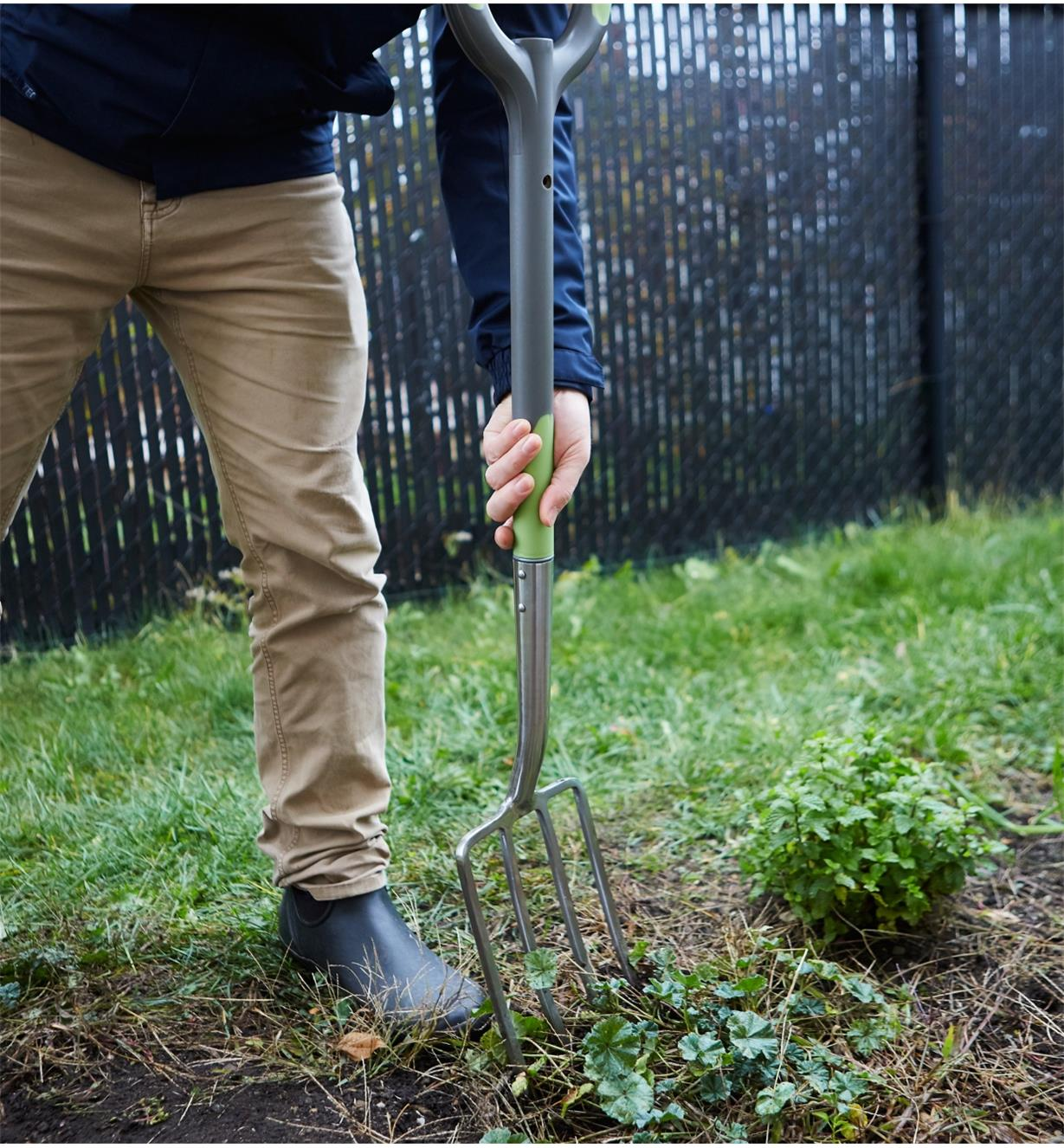 A man digs in a garden using the Radius Ergonomic Stainless-Steel Digging Fork