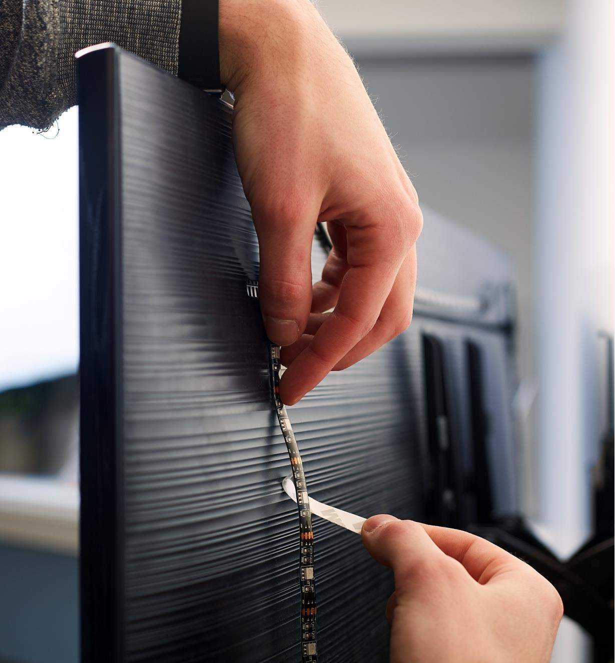 Personne retirant la pellicule protectrice du revers autocollant d'un luminaire-ruban à DEL USB pour le fixer derrière un téléviseur.