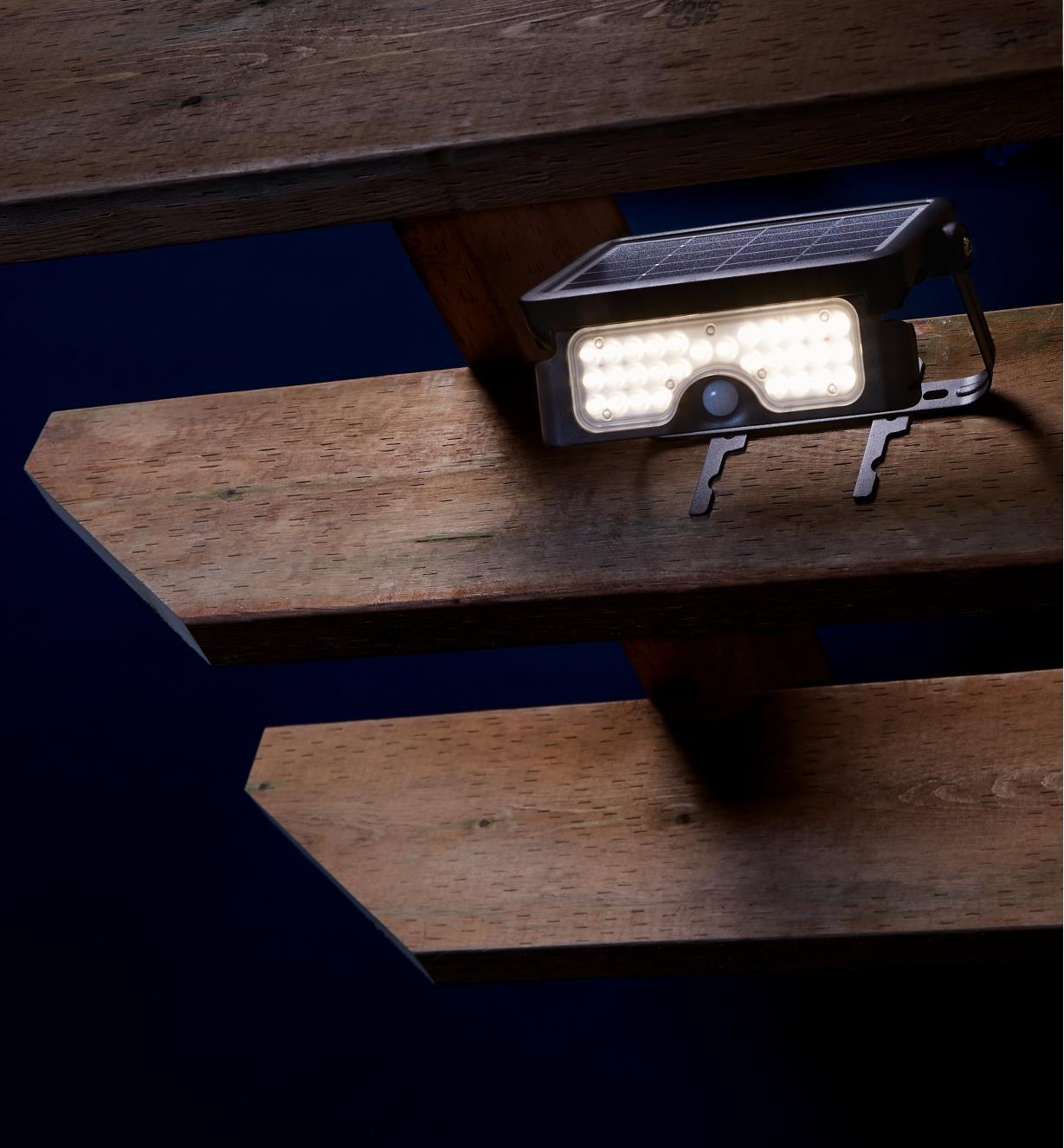 Lampe DEL solaire à détecteur de mouvement installée en hauteur sur une pergola