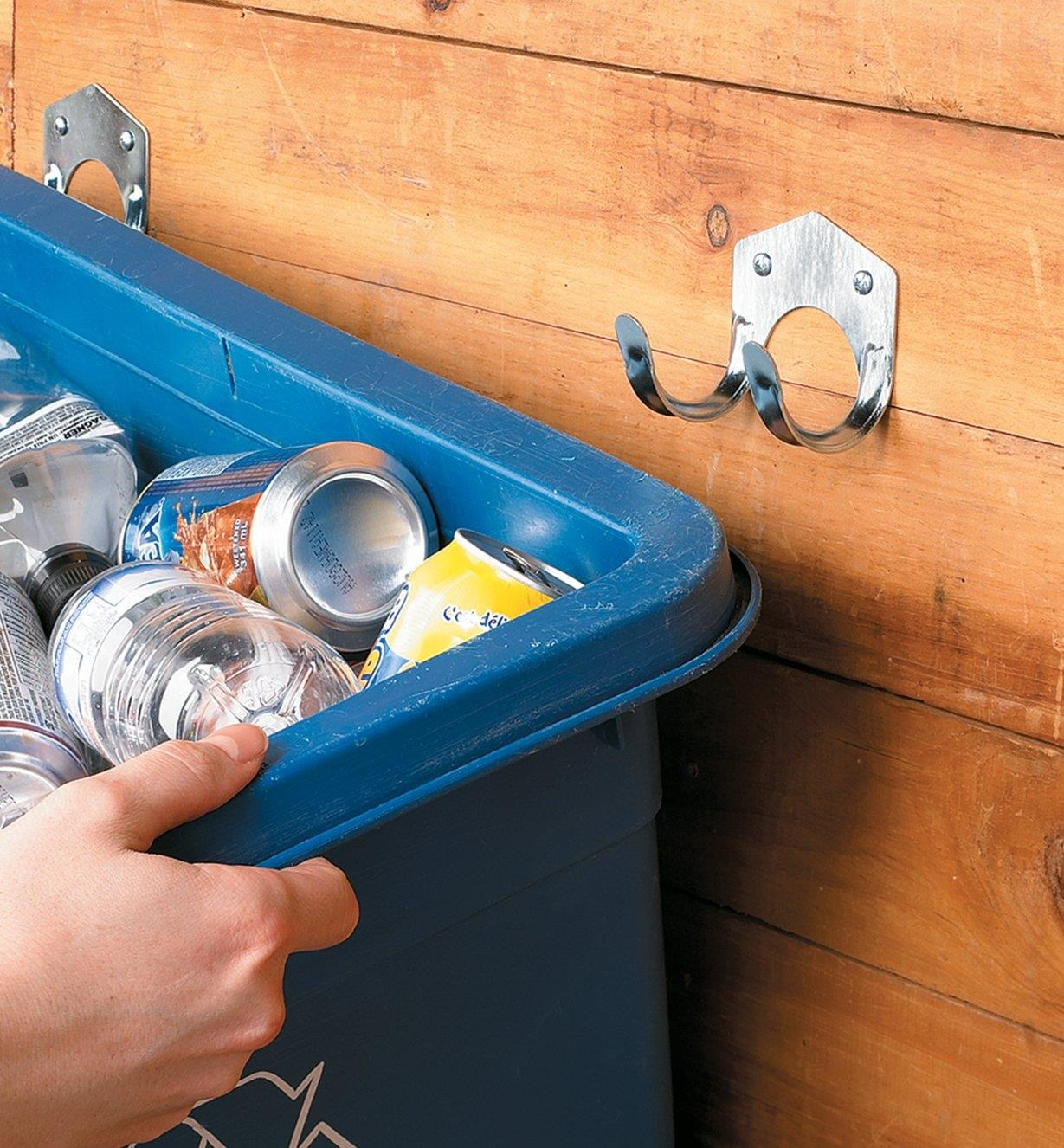 Two double hooks holding a recycling bin on a wall