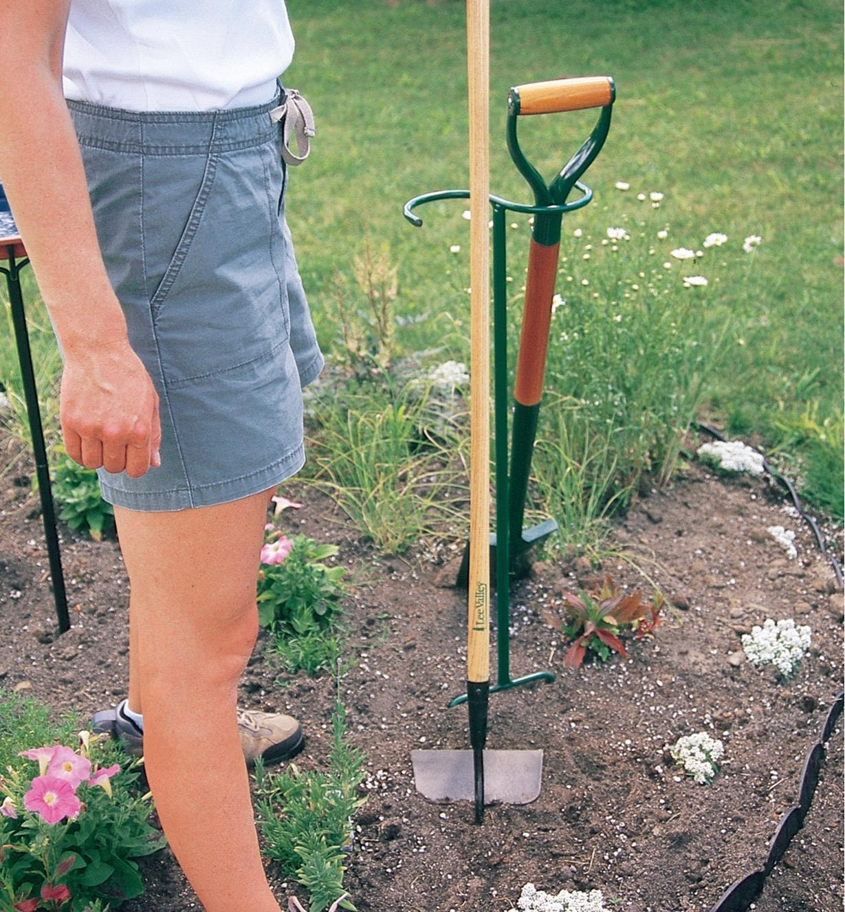 A woman leans a hoe against a Macgregor Tool Butler installed in a garden