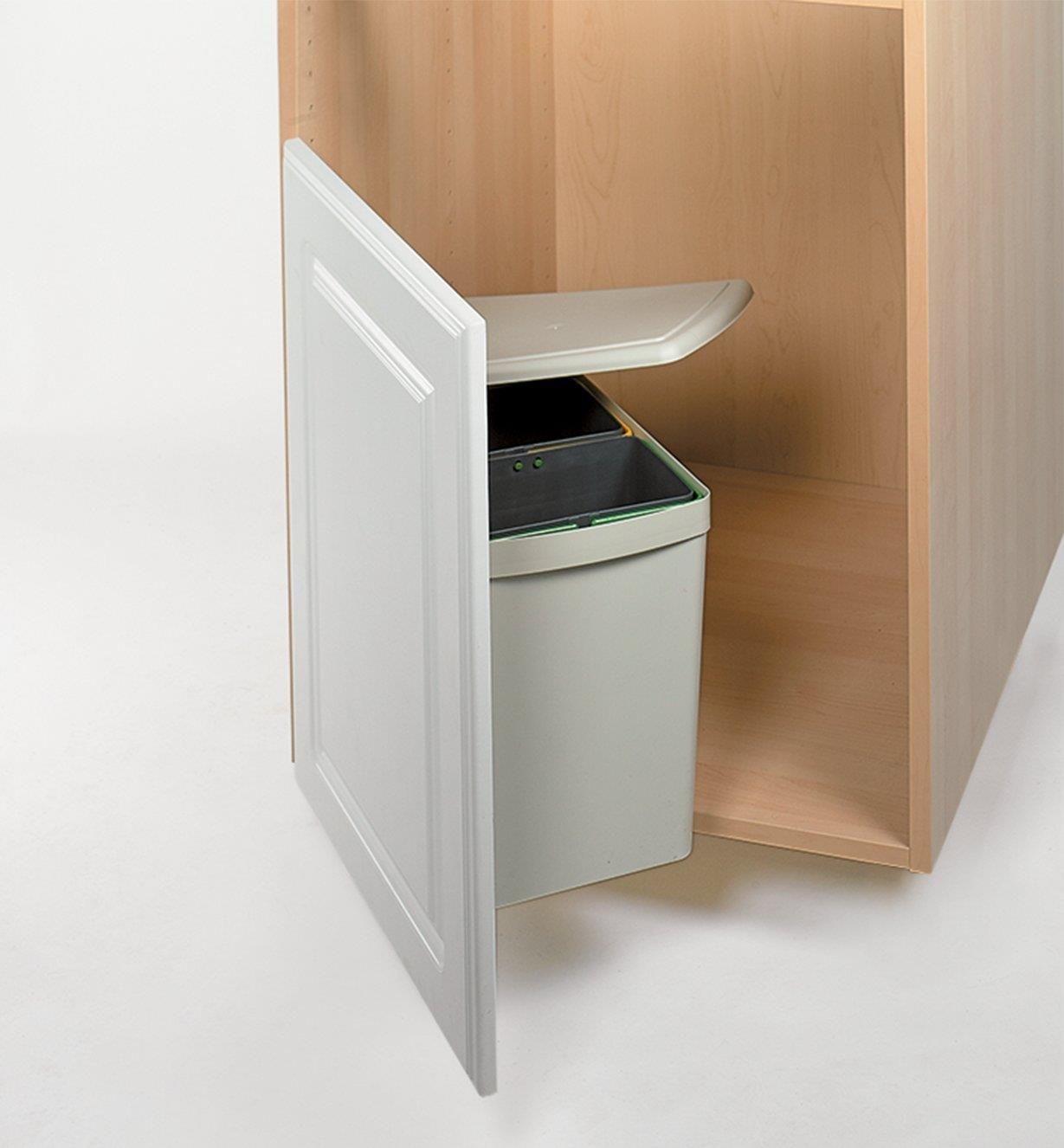 Cover of the waste container lifting as the cupboard door is opened