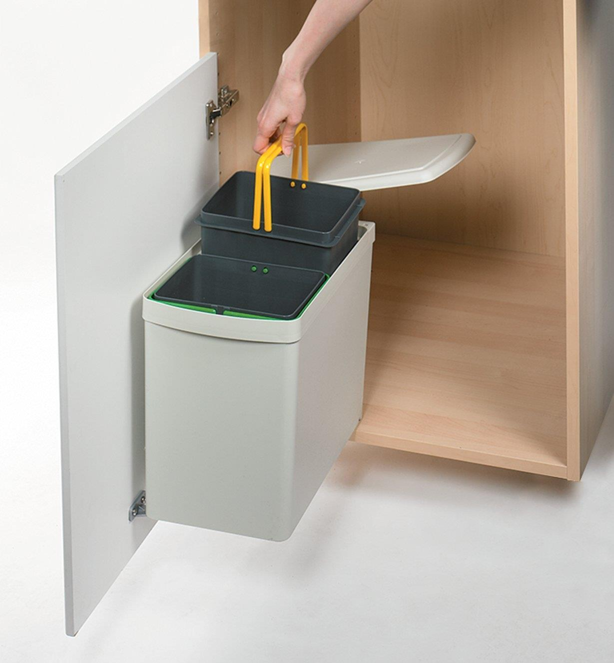 Lifting one of the bin inserts from the waste bin by the handles