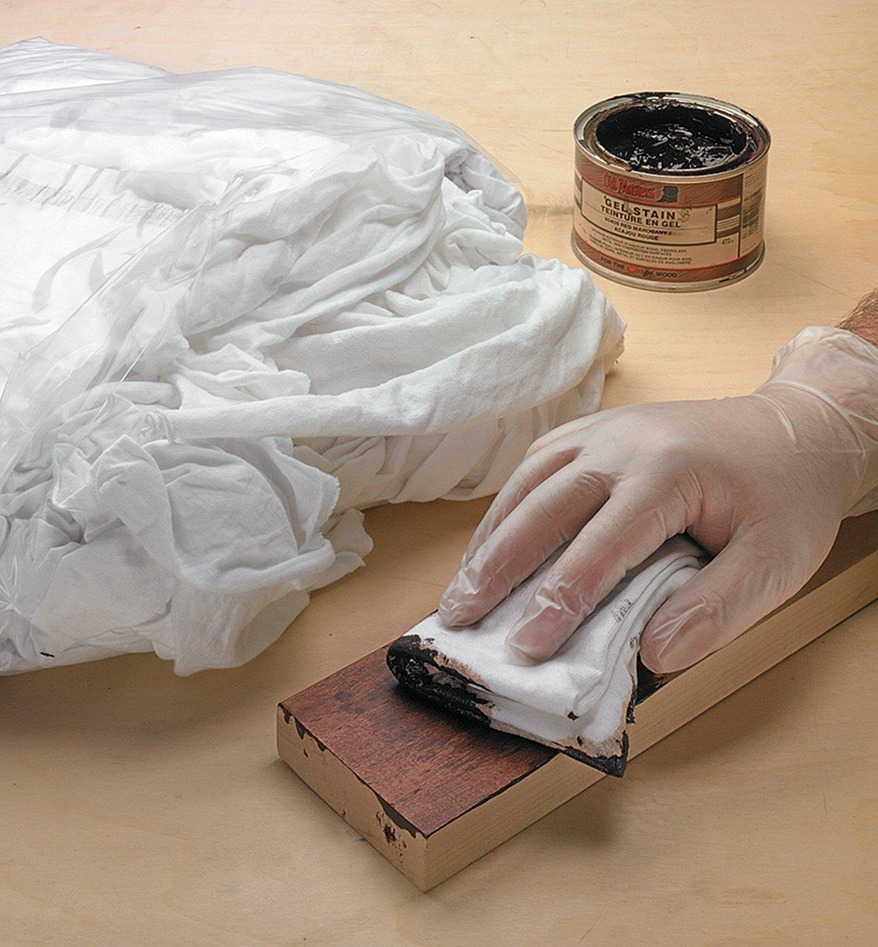 Applying stain to a strip of wood with an absorbent cotton wipe